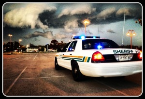 Photo of Sheriff patrol vehicle in parking lot with storm clouds in the distance
